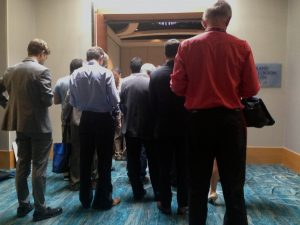 "Attendees stand outside the crowded ""News Content: What Works?"" session."